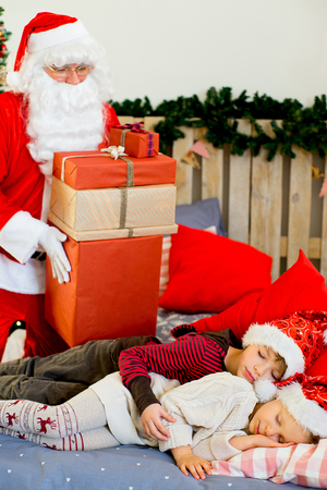 sneaks: Santa Claus quietly came to the children who are sleeping lying on decorated bed with Christmas tree in the background