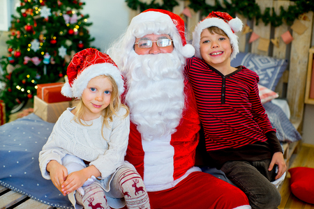 Santa Claus and two children sitting on a decorated bed and talking to each other