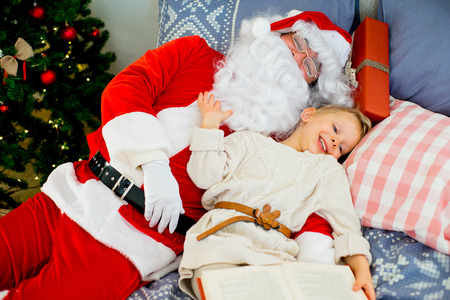 Santa Claus and cute girl getting ready for Christmas on the decorated bed near the christmas tree