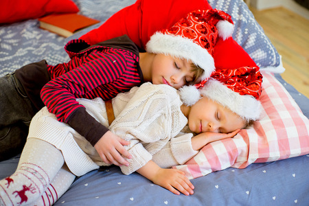 two children get sleepy till they await christmas lying on decorated bed