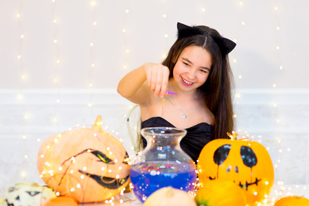 Teenager girl in cat costume posing with pumpkins and bottle of blue potion during Halloween party Stock Photo