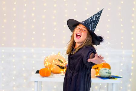 pocima: chica adolescente posando en traje de bruja con las calabazas y botella de poción azul durante la fiesta de Halloween