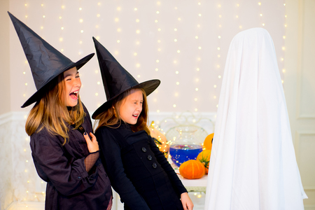 Group of teenagers wearing Halloween costumes fear of ghost, near the table with pumpkins and bottle of potion at haloween party Stock Photo