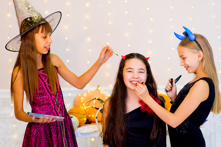 Happy group of teenagers in costumes preparing for Halloween, near the table with pumpkins and bottle of potion Stock Photo