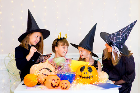Happy group of teenagers in costumes preparing for Halloween, playing around the table with pumpkins and bottle of potion