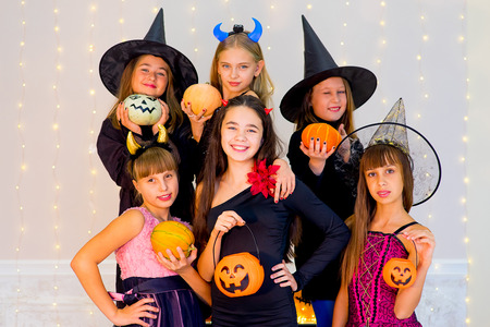 brincando: Happy group of teenagers in Halloween costumes posing on camera with pumpkins, smiling and joking Foto de archivo