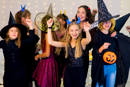Happy group of teenagers dance in Halloween costumes during the Halloween party with pumpkins Stock Photo