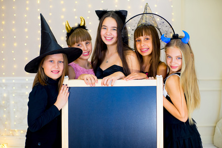 haloween: Group of teenagers wearing Halloween costumes posing with black board, smiling and laughing at haloween party