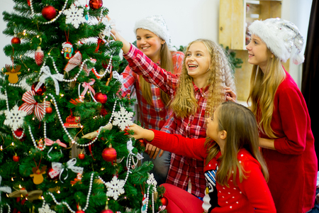 Happy girls in red hats decorate the Christmas tree in beautiful room Foto de archivo