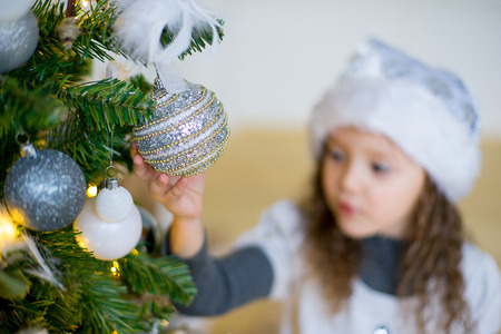 portrait of a girl with a Christmas hat near Christmas tree in the white room Stock Photo
