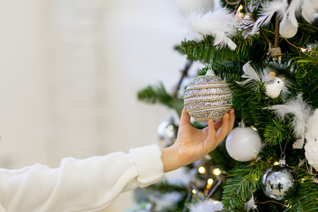 decorate: Happy girl decorate the Christmas tree in beautiful room Stock Photo