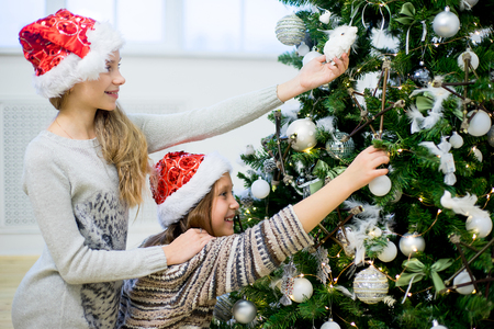 decorate: Two happy girls decorate the Christmas tree in beautiful room Stock Photo