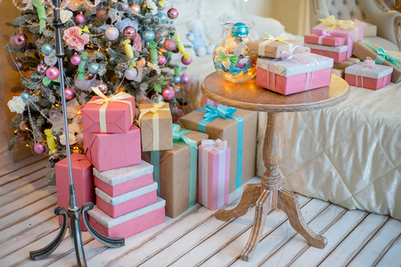 Christmas tree with gifts beside the bed, floor lamp, wrought iron chairs and table. Christmas interior in pastel colors