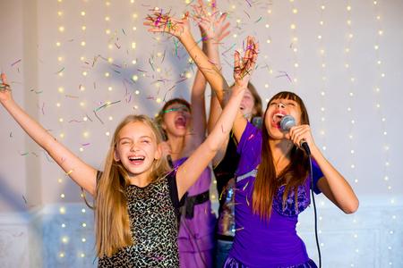 ヘッドフォン ライトの背景にカラオケで一緒に歌って幸せな女の子のグループ