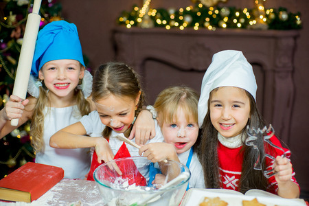 pastry cutters: kids baking christmas cookies before the celebration of Christmas. Family