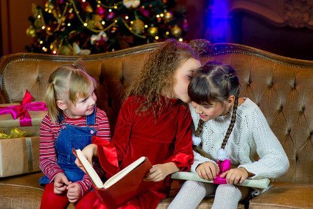 Santa Claus and group of girls sitting in Christmas room and reading a book. Christmas home decor