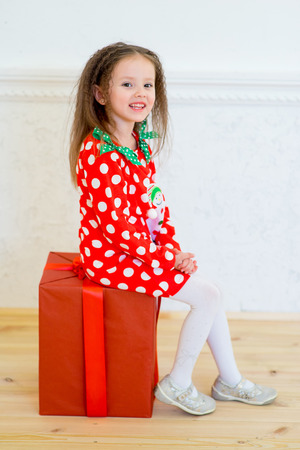 Happy little smiling girl with christmas gift box. Christmas interior Stock Photo