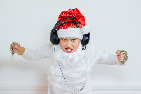 boy pretending he is a Bad Santa with chains, headphones Stock Photo