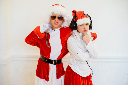 two boys pretending he is a Bad Santa with chains, headphones and sunglasses Stock Photo