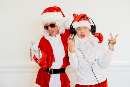 rudeness: two boys pretending he is a Bad Santa with chains, headphones and sunglasses Stock Photo