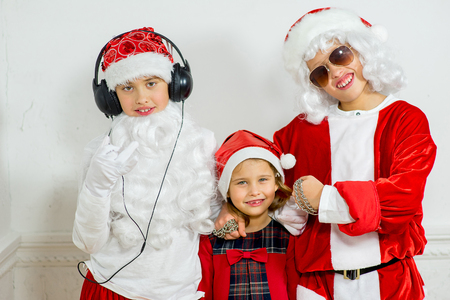 rudeness: two boys and little girl pretending he is a Bad Santa with chains, headphones and sunglasses