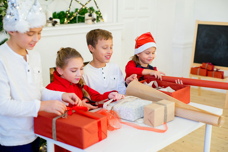 group of kids preparing gifts for christmas at home, cozy holiday interior