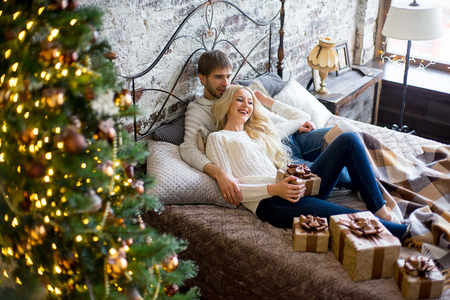 pullovers: Happy couple of lovers in white sweaters give each other gifts lying on the bed. Christmas tree and new year gift at home. Young family together