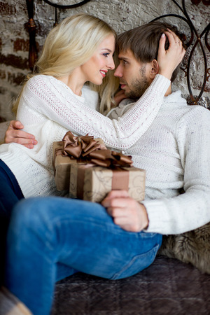 pullovers: Happy couple of lovers in white sweaters give each other gifts lying on the bed. Christmas and new year gift at home. Young family together