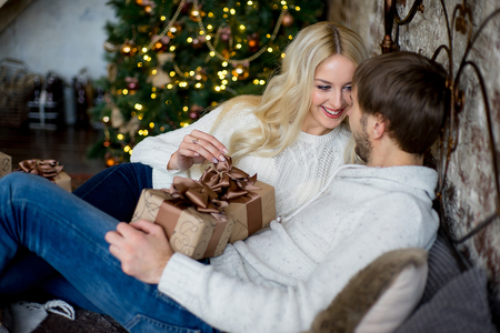 Happy couple of lovers in white sweaters give each other gifts lying on the bed. Christmas tree and new year gift at home. Young family together