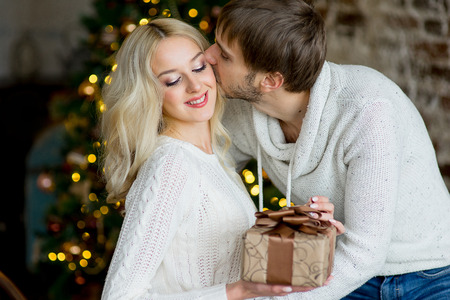 pullovers: Happy couple of lovers in white pullovers give each other gifts sitting on the bed. Christmas tree and new year gift at home. Young family together Stock Photo