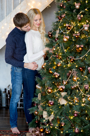 pullovers: Happy couple of lovers in pullovers decorating Christmas tree. Christmas and new year at home. Young family together