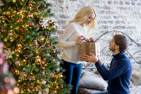 pullovers: man making a gift to the girl while they are decorating Christmas tree. Christmas and new year at home. Young family together