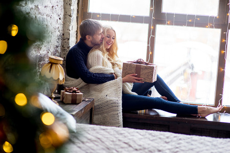 pullovers: Happy couple of lovers in pullovers give each other gifts sitting on the windowsill. Christmas and new year gift at home. Young family together Stock Photo