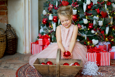 little girl looks at Christmas decorations sitting under the Christmas tree near a fireplace, a nice smile