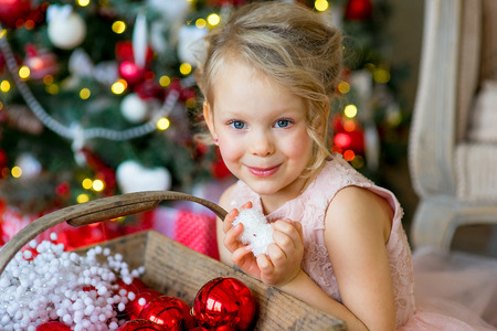 little girl looks at Christmas decorations sitting under the Christmas tree near a sofa, a nice smile