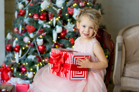 little girl in pink dress with Christmas gift sitting near Christmas tree, a nice smile