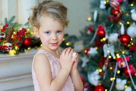 little girl looks at camera near the Christmas tree and a fireplace, a nice smile