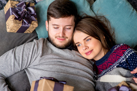 pullovers: Couple of lovers in pullovers and wool socks lying on the sofa. Christmas time. Holiday at home Stock Photo