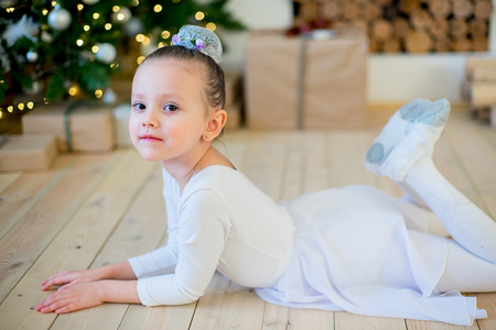 Young ballet dancer lying near Christmas tree on the wooden floor and smile