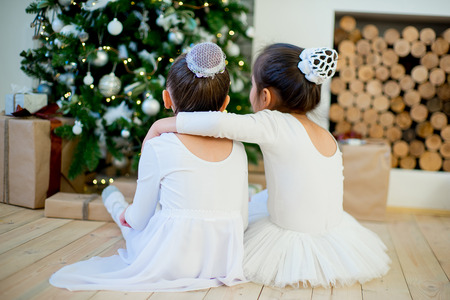 Two young ballet dancer sitting near Christmas tree on the wooden floor. Back Foto de archivo