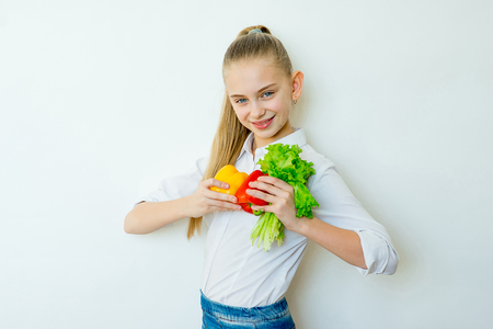 Happy fitness girl holding vegetables isolated