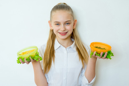 Happy fitness girl holding canned peas and corn Stock Photo