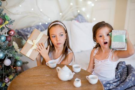 niños desayunando: Child girls wake up in her bed in Christmas morning