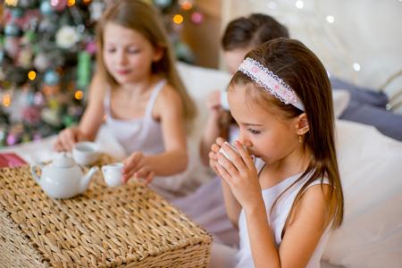 niños desayunando: Niñas se despiertan en su cama en la mañana de Navidad Foto de archivo