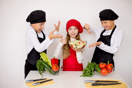attempt: three young chefs evaluate a salad isolated