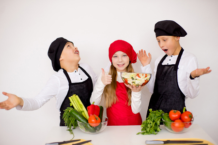 three young chefs evaluate a salad isolated