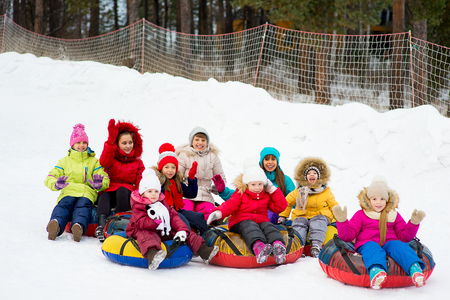 Kids on snow tubes downhill at winter day