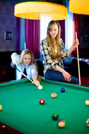 socializando: Dos niñas jugando al billar Foto de archivo