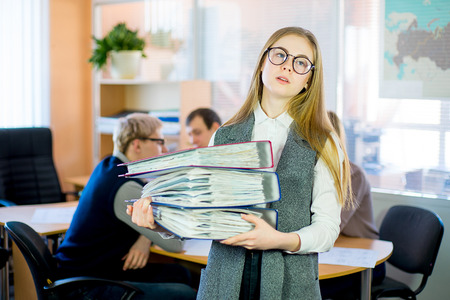 girl holding a stack of documents Stock Photo