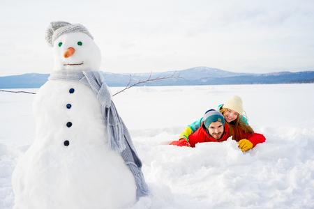 Happy couple lying in snow